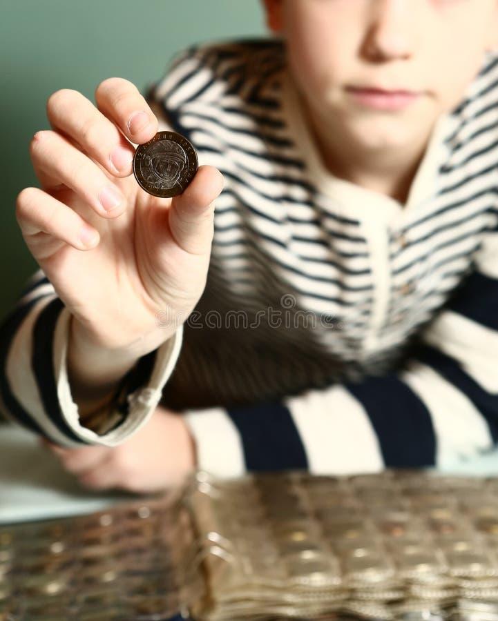Pojke med myntsamlingen Pojkecollectioner royaltyfri foto