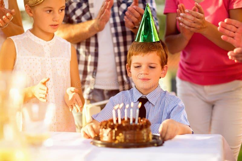 Pojke med partihatten och födelsedagkakan fotografering för bildbyråer