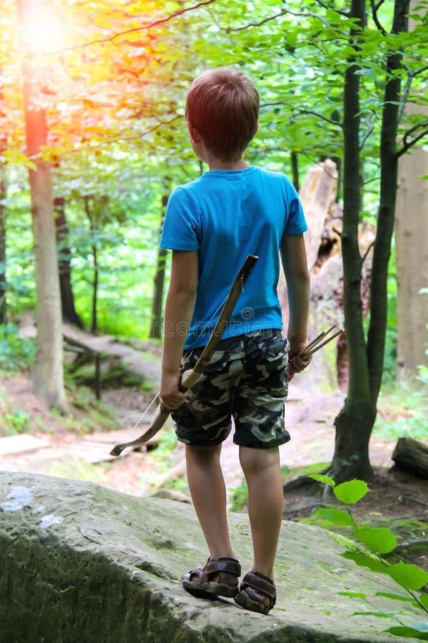 Pojke med pilbågen och pilar på en gå i parkera fotografering för bildbyråer