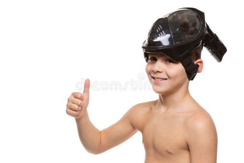 Pojke med rakt framifrån att dyka maskeringen på hans huvud, pojke som ler och visar en intyga gest, på en vit bakgrund, kopierin royaltyfri bild