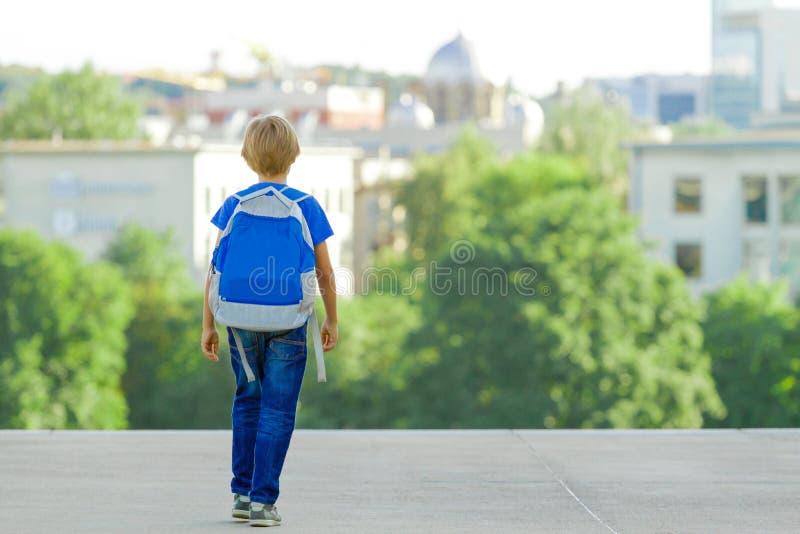 Pojke med ryggsäcken på stadsgatan Dra tillbaka till skolan, utbildning, folket, loppet, fritidbegrepp arkivfoto