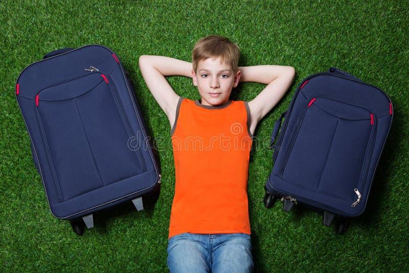 Pojke med siutcasesth som ligger på grönt gräs royaltyfria foton