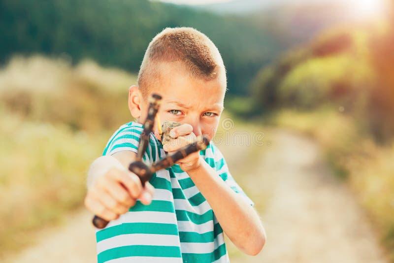 Pojke med slingshoten royaltyfri bild