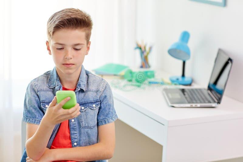 Pojke med smartphonen som trakasseras av textmeddelandet arkivfoton