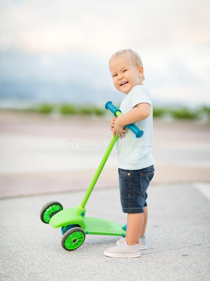 Pojke med sparkcykeln royaltyfri fotografi