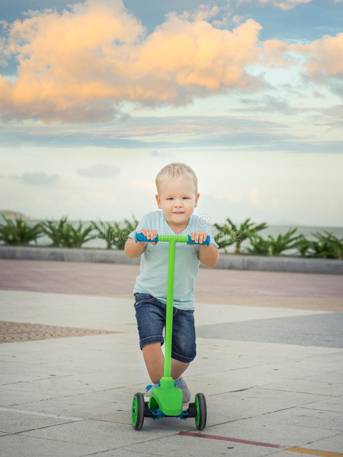 Pojke med sparkcykeln arkivfoton