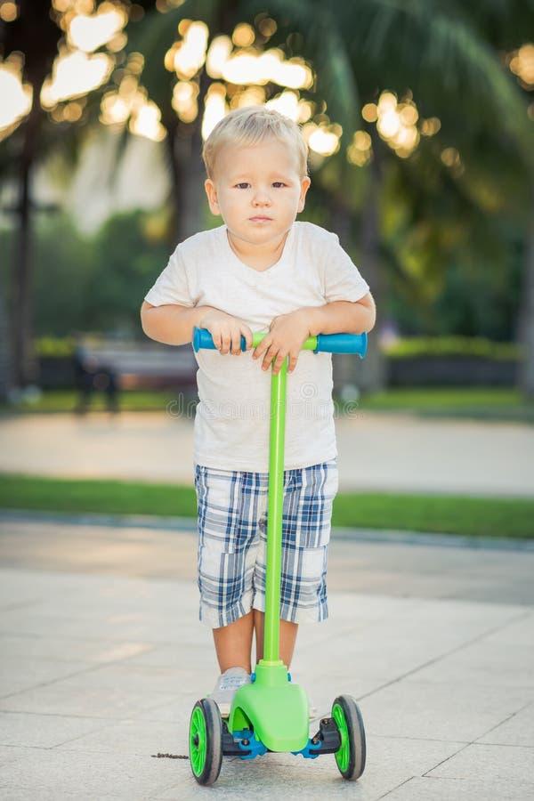 Pojke med sparkcykeln arkivfoto