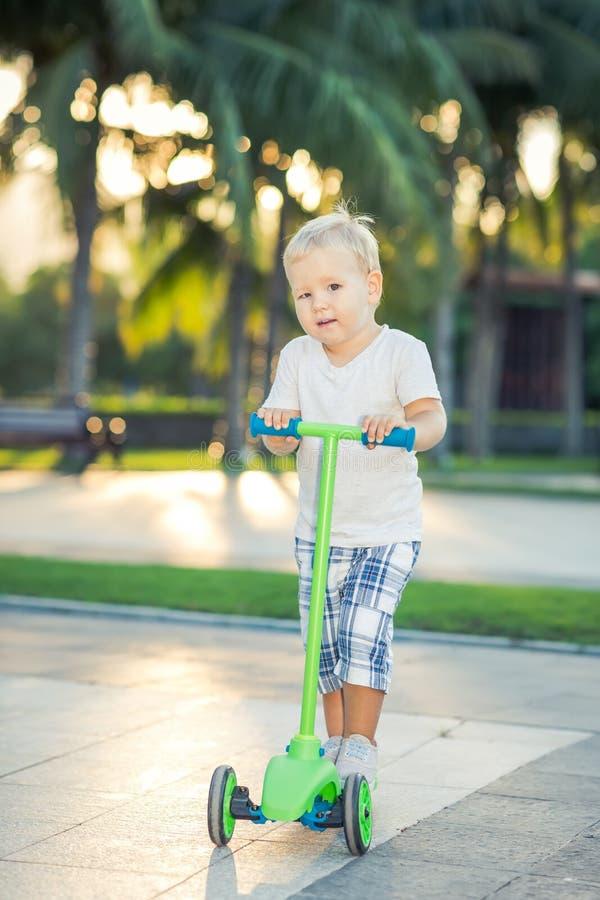 Pojke med sparkcykeln royaltyfri foto