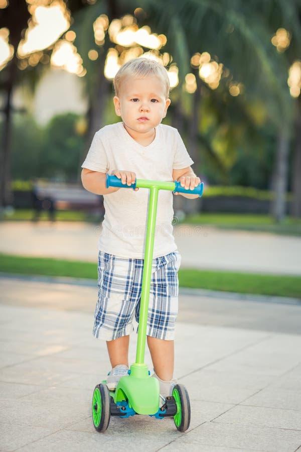 Pojke med sparkcykeln royaltyfria bilder