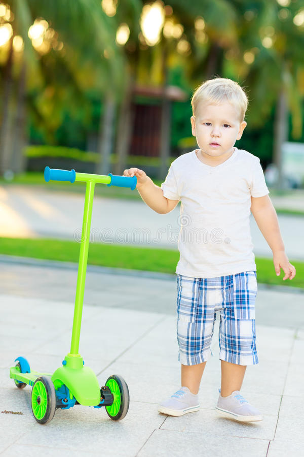 Pojke med sparkcykeln royaltyfri bild