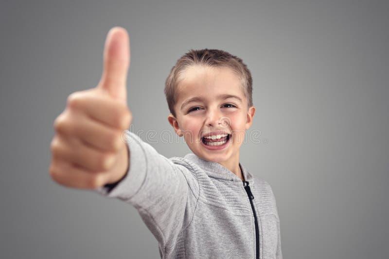 Pojke med tummar som instämmer upp royaltyfri foto