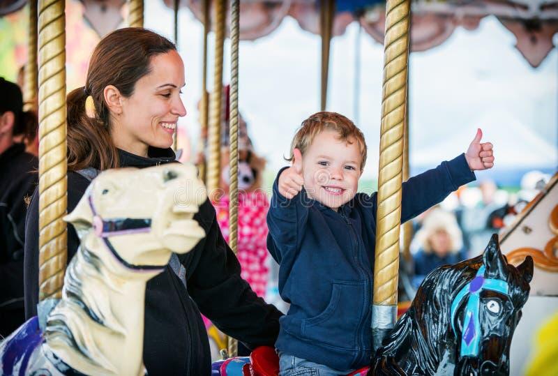 Pojke med två tummar upp med modern på karusell arkivbild
