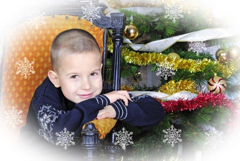 Pojke nära en julgran med gåvor fotografering för bildbyråer