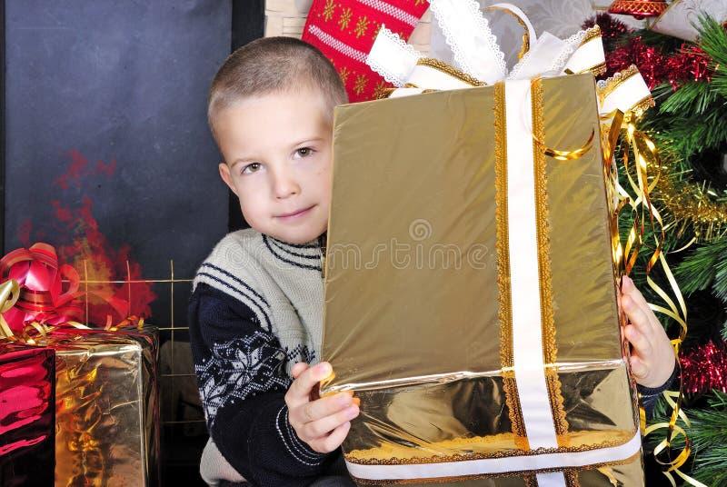 Pojke nära en julgran med gåvor royaltyfri fotografi