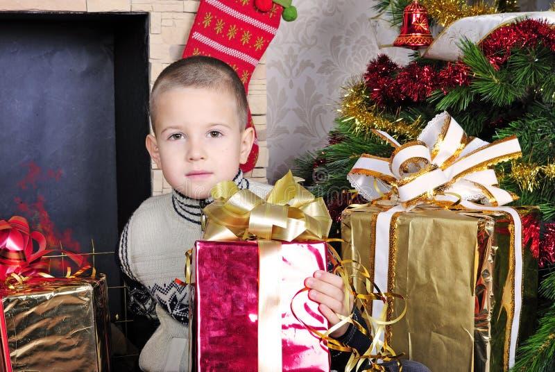 Pojke nära en julgran med gåvor royaltyfri foto