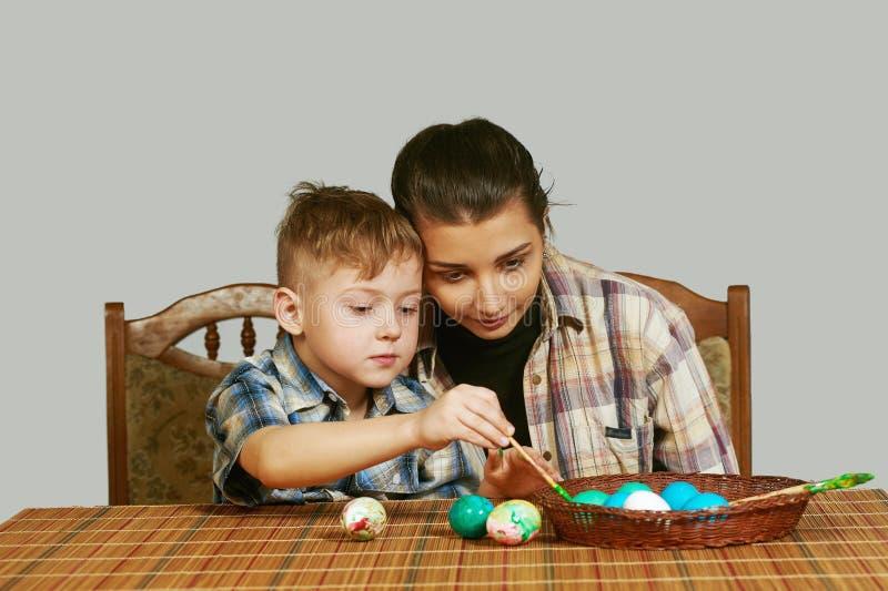 Pojke och äldre ägg för systerfärgläggningpåsk arkivbilder