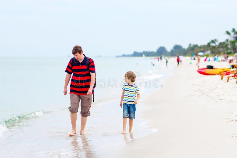 Pojke och fader för liten unge som har gyckel med att samla skal fotografering för bildbyråer