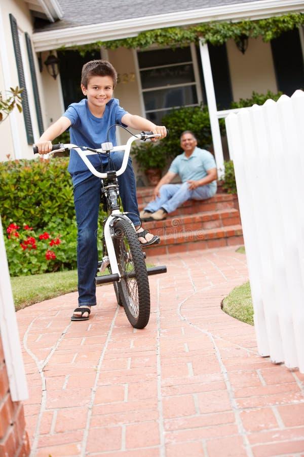 Pojke och farfar med cykeln arkivbild