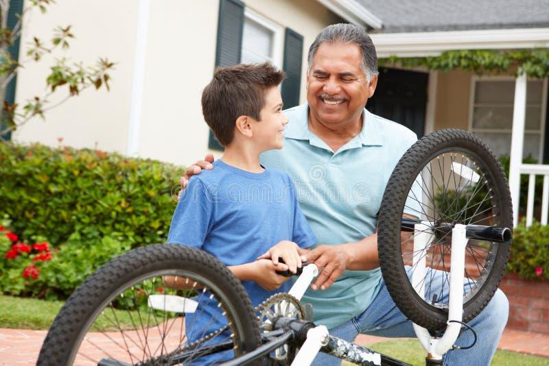 Pojke- och farfarreparationen cyklar tillsammans royaltyfri foto