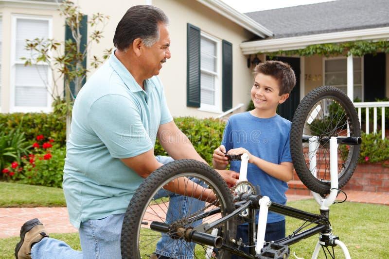 Pojke- och farfarreparationscykel royaltyfria foton
