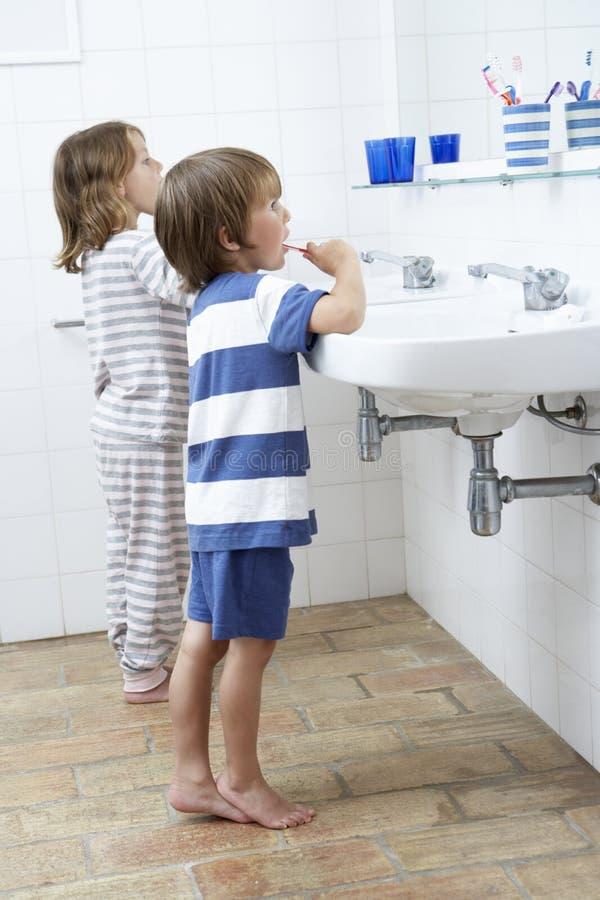 Pojke och flicka i badrum som borstar tänder royaltyfri foto