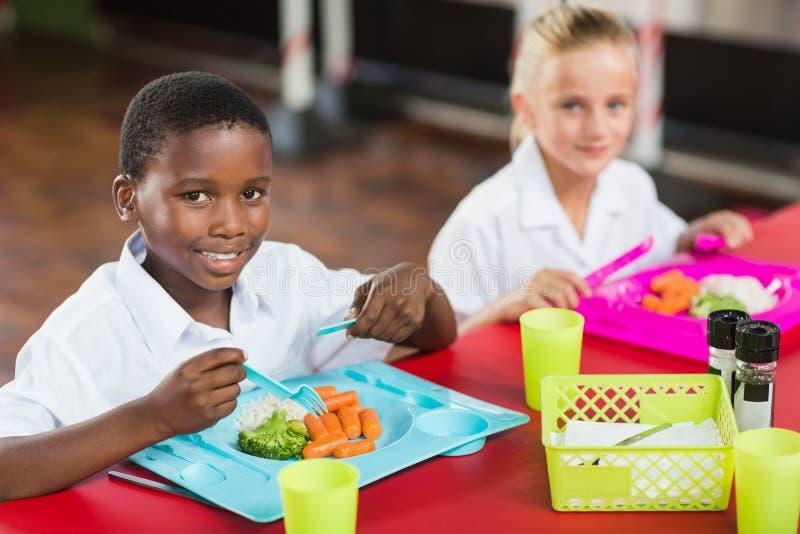 Pojke och flicka i skolalikformig som har lunch i skolakafeteria royaltyfri foto