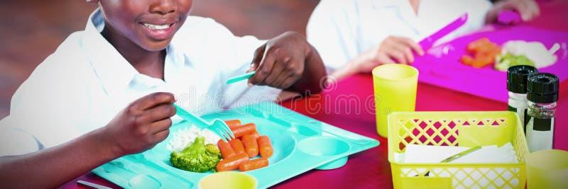 Pojke och flicka i skolalikformig som har lunch i skolakafeteria arkivbilder