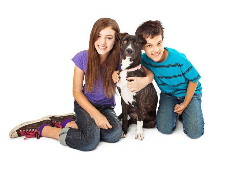 Pojke och flicka med den nya hunden arkivfoto
