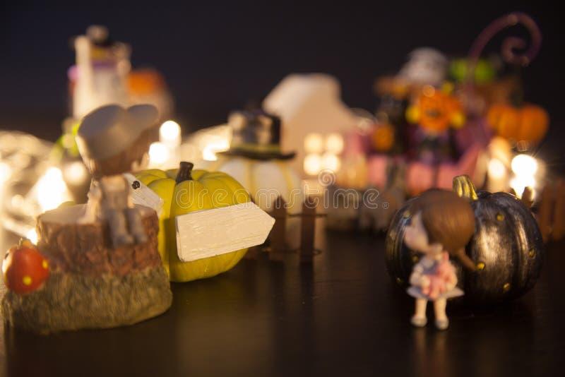 Pojke och flicka på den gula guld- pumpaporten med tom vit pilteckenvälkomnande till huset för allhelgonaaftonfestivalparti Festl arkivbilder