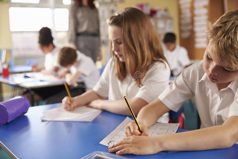 Pojke och flicka som arbetar i grundskola för barn mellan 5 och 11 årgrupp, slut upp arkivbilder