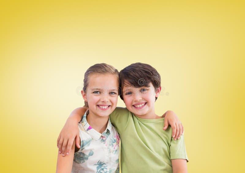 Pojke och flicka som framme kramar av gul bakgrund arkivbilder