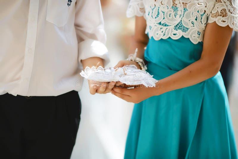 Pojke och flicka som ger en cirkelkudde, tillbehör för bröllopdag för brudar royaltyfria foton