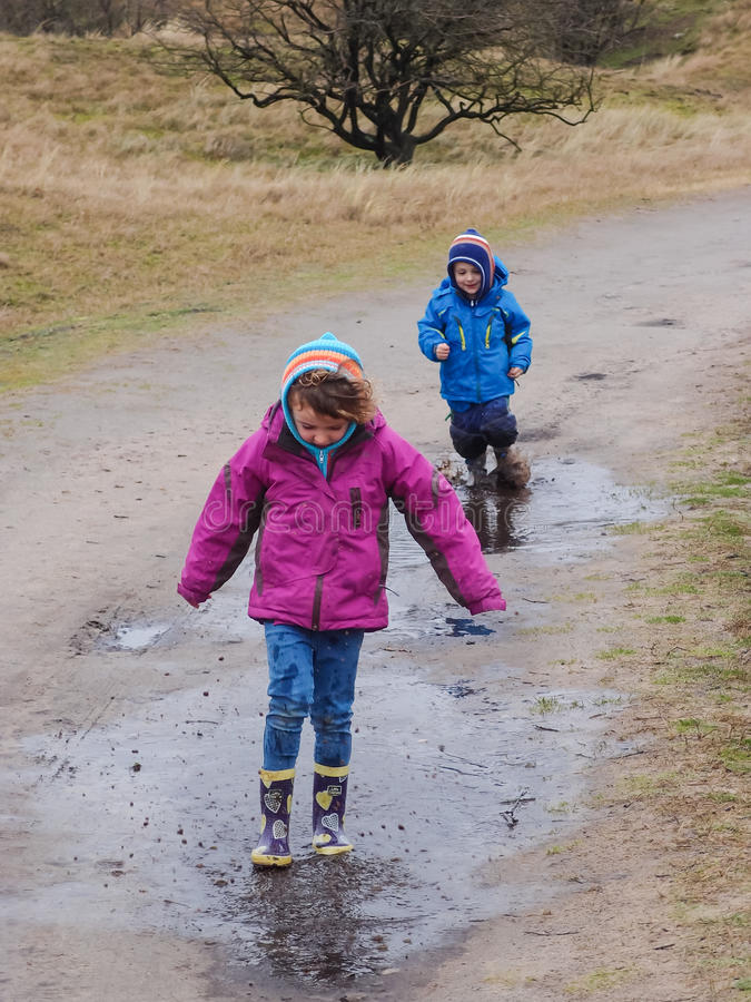 Pojke och flicka som plaskar i en lerig pöl royaltyfri bild