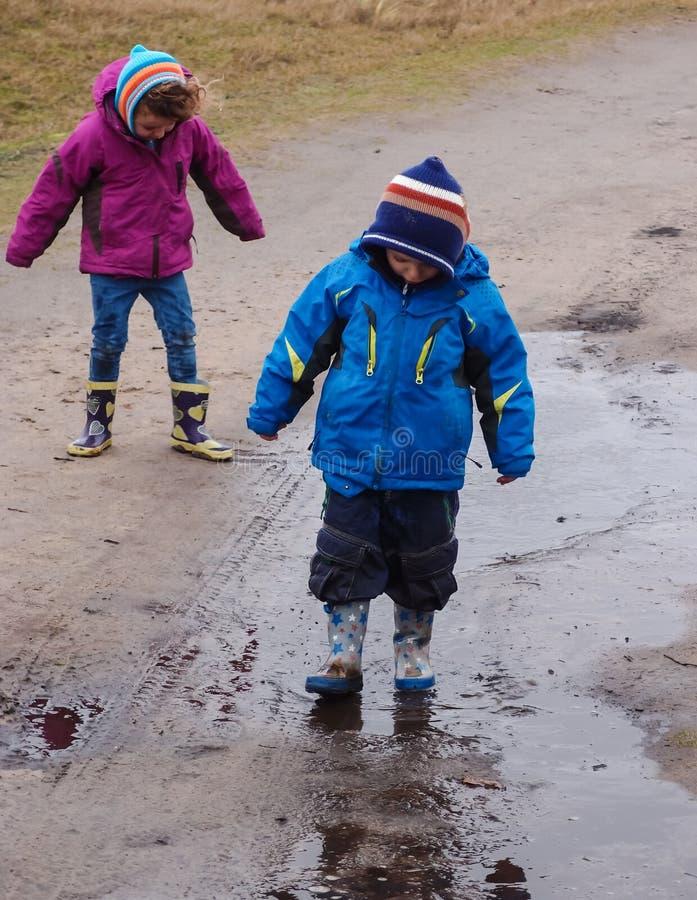 Pojke och flicka som plaskar i en lerig pöl royaltyfri foto