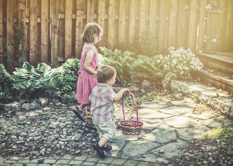 Pojke och flicka som söker efter Retro påskägg - arkivfoton