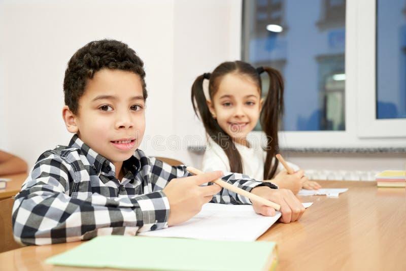 Pojke och flicka som sitter på skrivbordet i klassrumet som poserar royaltyfria bilder