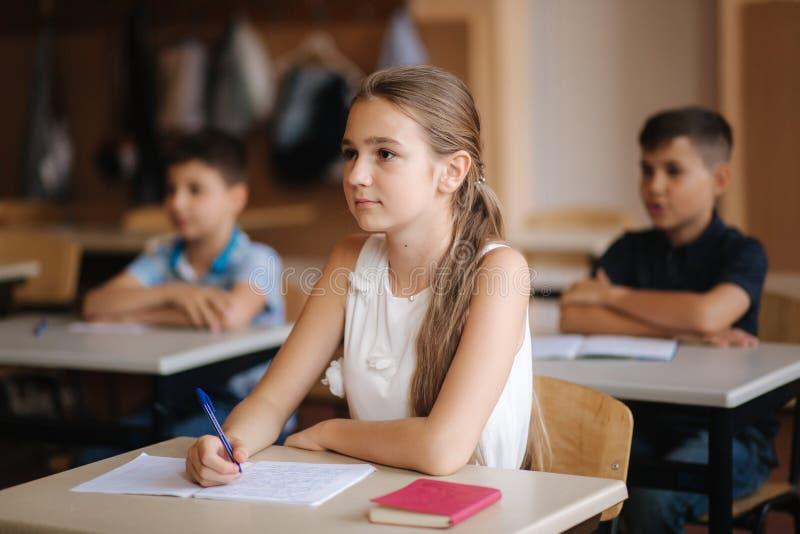 Pojke och flicka som sitter på skrivbordet och skriver en text royaltyfri foto