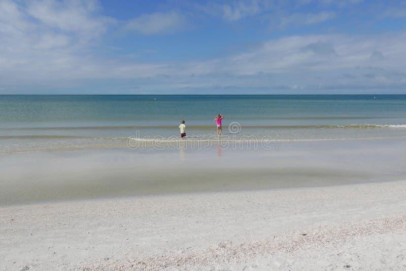 Pojke och flicka som spelar i vattnet på St Pete Beach, Florida, USA royaltyfri bild