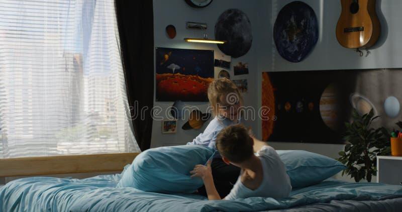 Pojke och flicka som spelar kuddekamp p? s?ng arkivbild