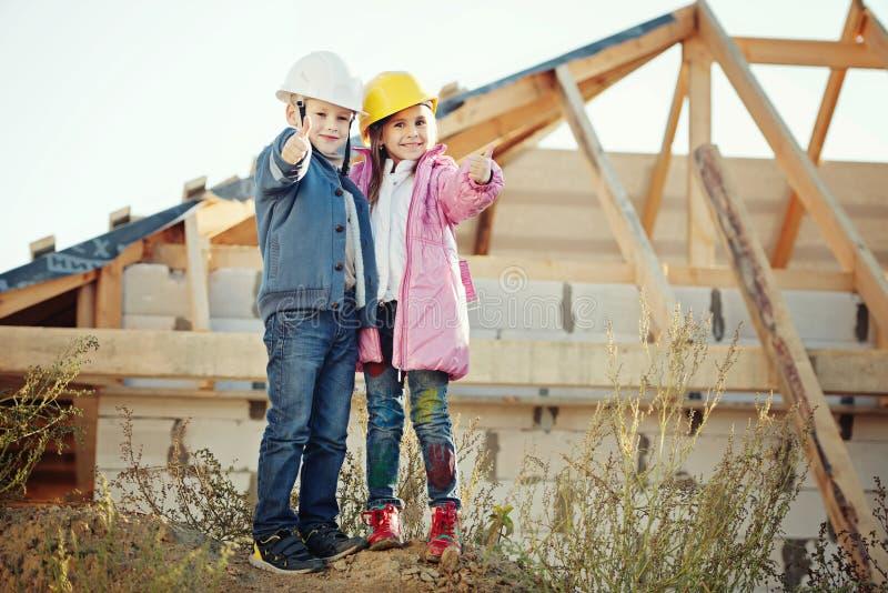 Pojke och flicka som spelar på konstruktionsplats arkivbilder