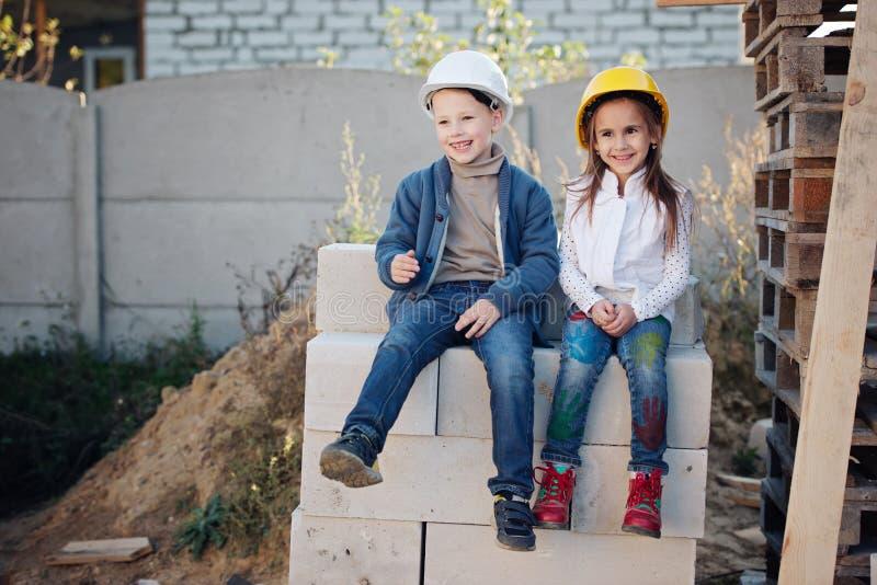 Pojke och flicka som spelar på konstruktionsplats royaltyfria bilder