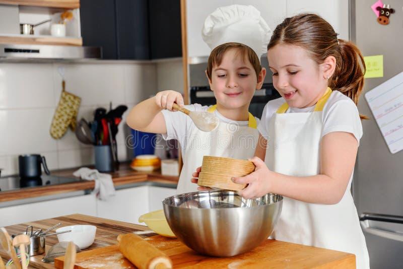 Pojke och flicka som tillsammans bakar i det hem- köket arkivbilder