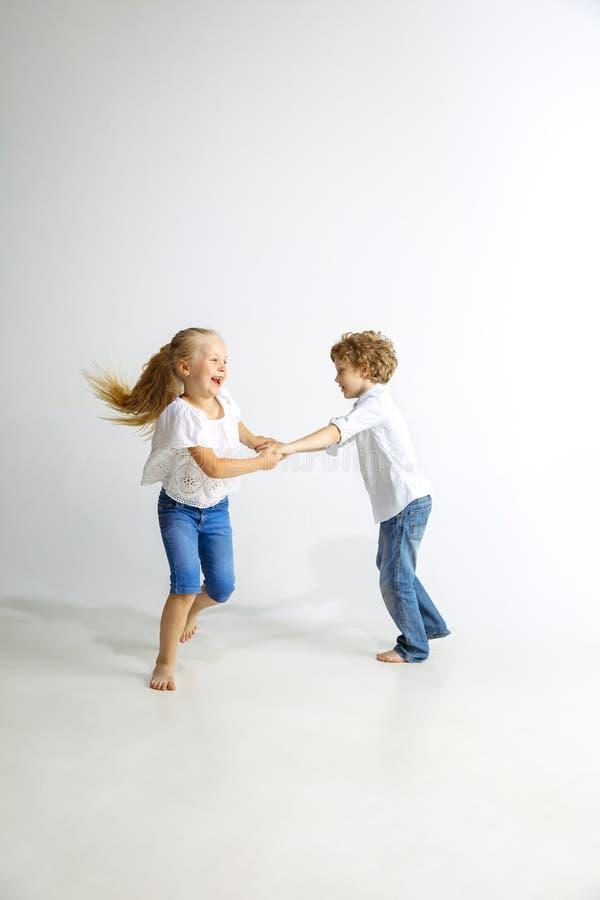 Pojke och flicka som tillsammans spelar på vit studiobakgrund royaltyfri foto