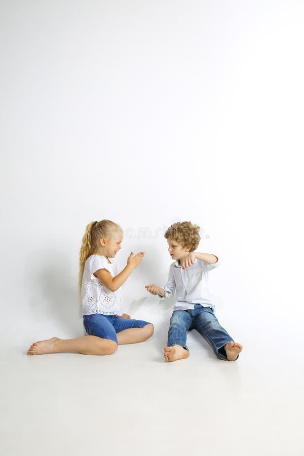 Pojke och flicka som tillsammans spelar på vit studiobakgrund royaltyfri fotografi