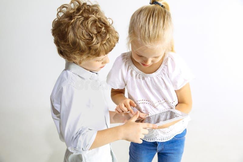 Pojke och flicka som tillsammans spelar på vit studiobakgrund royaltyfri bild