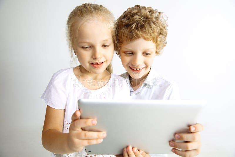 Pojke och flicka som tillsammans spelar på vit studiobakgrund arkivbild