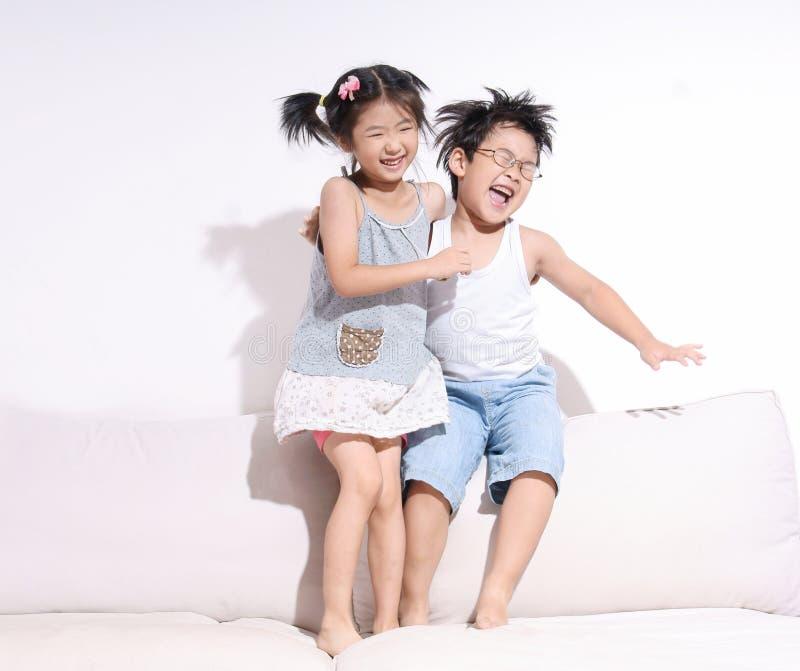 Pojke- och flickabanhoppning och skratta på sofaen royaltyfri foto