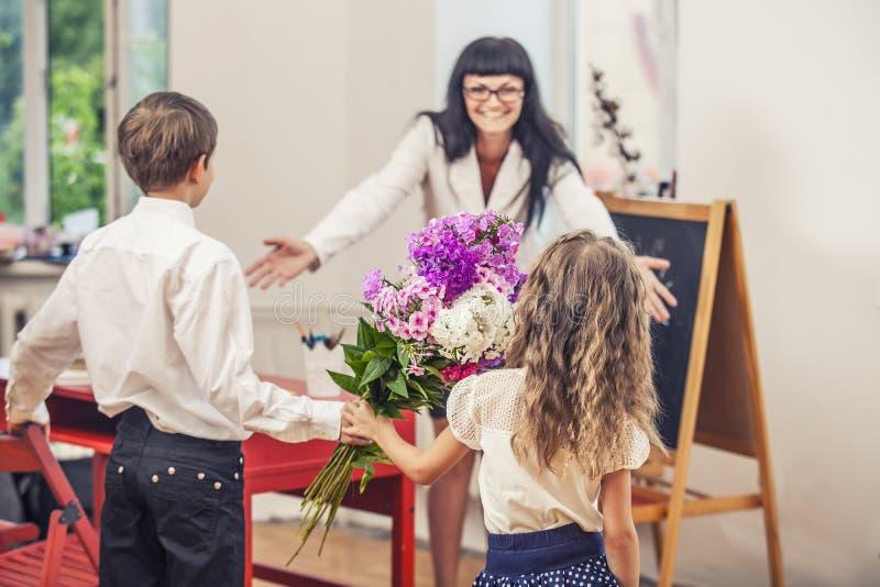 Pojke- och flickabarn ger blommor som en skolalärare i teache royaltyfri bild