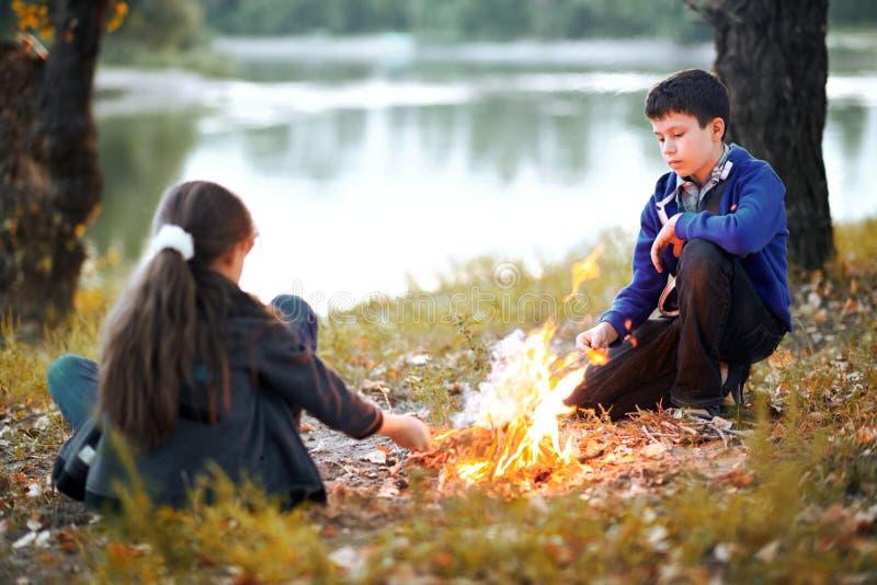 Pojke- och flickasammanträde på flodbanken, gör en brand, höstskogen på solnedgången, den härliga naturen och reflexion av träd i royaltyfri fotografi