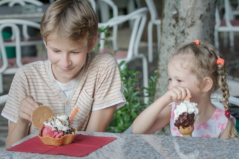 Pojke- och flickaungar som tycker om deras italienska glass i gelateria fotografering för bildbyråer